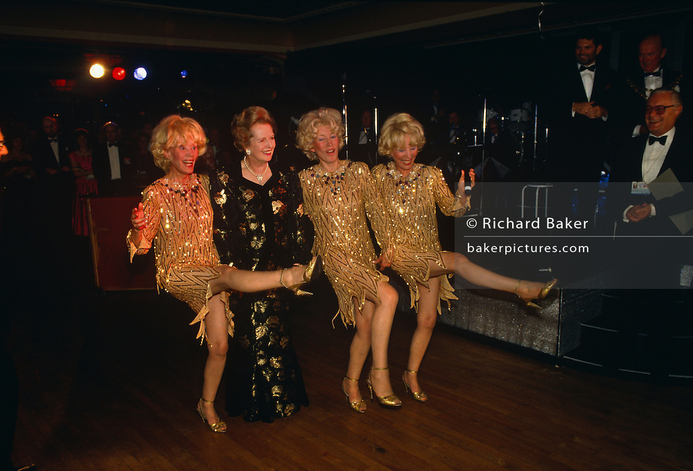 Prime Minister Margaret Thatcher is seen dancing with a Tory Party official during the 1990 Conservative Party conference in Blackpool. Thatcher is wearing a favourite black and red ball gown and is the centre of attention for delegates and media. She is seen with Joy, Babs and Teddie - otherwise known as the Beverly Sisters entertainers, the  longest surviving vocal group of all time without a change in the line up. The sisters kick their legs up in the air dancing the Charleston (though not in unison) but Mrs Thatcher in her long dress declines and merely stands straight-legged. They are on the dance floor and Tory party officials are enjoying the moment as their PM relishes the moment.