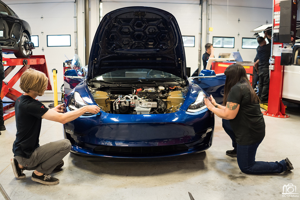Brandon Christie of Sonora installs a Tesla Model 3 bumper with the help of Tesla Start instructor Natalie Flores during the Tesla Start class at Evergreen Valley Community College in San Jose, California, on August 8, 2019. (Stan Olszewski for Silicon Valley Business Journal)
