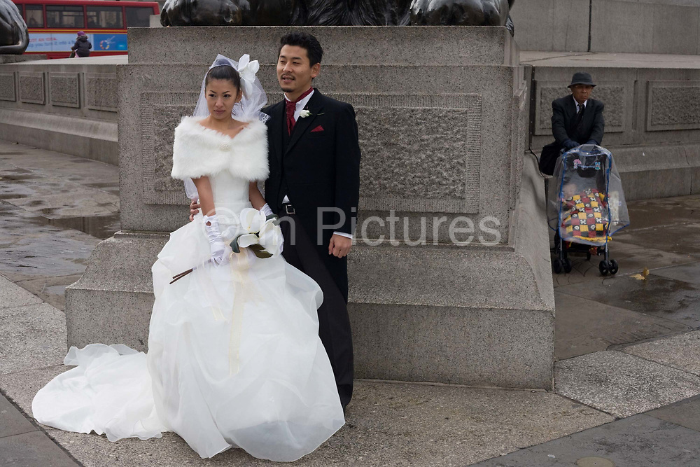 A Chinese couple pose for their wedding portraits beneath Nelson's Column in central London's Trafalgar Square. Hiding out of their view is a spectator and unbeknown to the newlyweds  the man guards a pushchair containing a young child. It is a chilly November day and the bride shivers in a skimpy wedding dress  her collar bone revealing she is slim and is probably very cold. Her new husband wears a traditional English long coat with tails and a cravat and button hole flower  possibly hired for this special occasion. Together the lady and man stand against stone of four granite corners on which four lions sit guarding the famous English sailor.