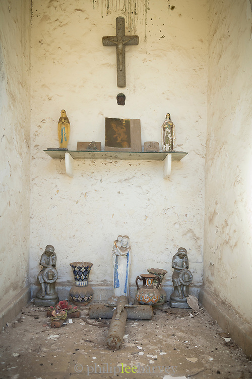 Composition of old cross and figurines of Virgin Mary at cemetery in Casablanca, Morocco
