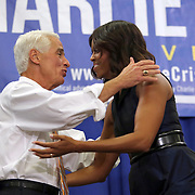 "First Lady Michelle Obama hugs Charlie Crist after speaking at his grassroots ""Commit to Vote"" rally at the Barnett Park Gymnasium in Orlando, Florida on Friday, Nov. 17, 2014. (AP Photo/Alex Menendez)"