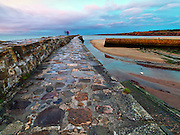 Saint Andrews Scotland Harbour with dramatic sunset and low tide with people walking and blurred on stone jetty. Licensing and Limited Editions of 17