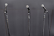 microphones standing besides a podium