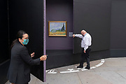 Before passing Extinction Rebellion Climate Change activists get too near, staff from the National Gallery cover copies of selected paintings, a temporary display of historical art placed outside the National Gallery to show passers-by what can be seen in their galleries, on 1st September 2021, in Trafalgar Square, London, England.