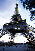 Eiffel Tower in evening with people walking underneath.
