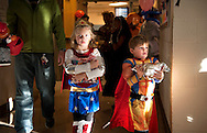 26 Oct 2013 -- ST. LOUIS -- Hollye Anne Brinkley (center) and her brother Henry Brinkley (right) carry their bags of candy while leaving the safe Halloween Party sponsored by St. Matthew Catholic Church in St. Louis Saturday, Oct. 26, 2013. The Brinkley family are parishioners at St. Matthew. Children from the surrounding Ville neighborhood played games to collect tickets to be exchanged for prizes, and upon leaving were given candy. Photo © copyright 2013 Sid Hastings.