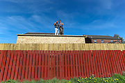 David (L) and Barry (R) are two Northern Irish construction workers who are pictured working on the rooftop of a private pub they were building for a private landlord on the East Side of the six meters Peace Wall in Belfast on Thursday, April 22, 2021. They're loyal to the United Kingdom but they said they never want to get back to dark times. David and Bary both have friends in West Belfast and don't mind socialising with republicans. (Photo/ Vudi Xhymshiti)
