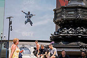 An image of a leaping figure from a Piccadilly Circus Calvin Klein ad whose slogan is Dare to Defy, and Londoners on Freedom Day. This date is what Prime Minister Boris Johnsons UK government has set as the end of strict Covid pandemic social distancing conditions with the end of mandatory face coverings in shops and public transport, on 19th July 2021, in London, England.