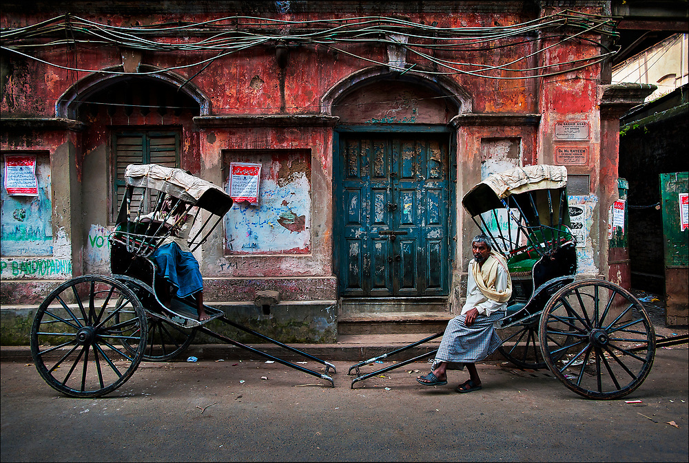 """Like a scene from the early twentieth century, rickshaw-pullers rest on a backstreet in Calcutta, now renamed Kolkata, in West Bengal State. The city's some 6,000 licensed rickshaw drivers are often called """"human horses"""" and generally earn less than $5 a day navigating the city's crowded and sometimes flooded streets. © Steve Raymer / National Geographic Creative"""