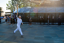 © Licensed to London News Pictures. 21/07/2012. London, UK.  London 2012 Olympics.  Sir Robin Knox-Johnson carries the Olympic Torch around the Cutty Sark ship in Greenwich, London.  Sailors from HMS Ocean stand in line alongside the Cutty Sark to cheer Sir Robin.  Sir Robin was the first person to to sail non-stop around the world, founded the Clipper Round the World Race in 1995, and has been a Cutty Sark Trustee since 2011. Photo credit : Richard Isaac/LNP