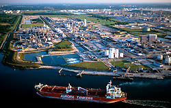 Aerial view of a tanker travelling by a refinery in Galveston Texas