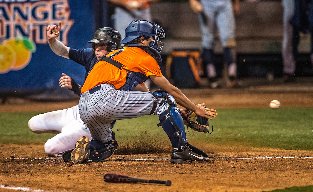 A close play at the plate as CSF catcher attempts to tag out Cypress player
