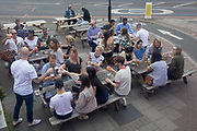 View from the top deck of a London bus, of outdoor drinkers siting on benches and raising theor glasses for a toast, outside a bar near Oval in south London, on 23rd May 2019, in London, England.