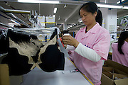A Chinese woman packs bras for export to the United States in the shipping area of the Top Form factory in Longnan, China