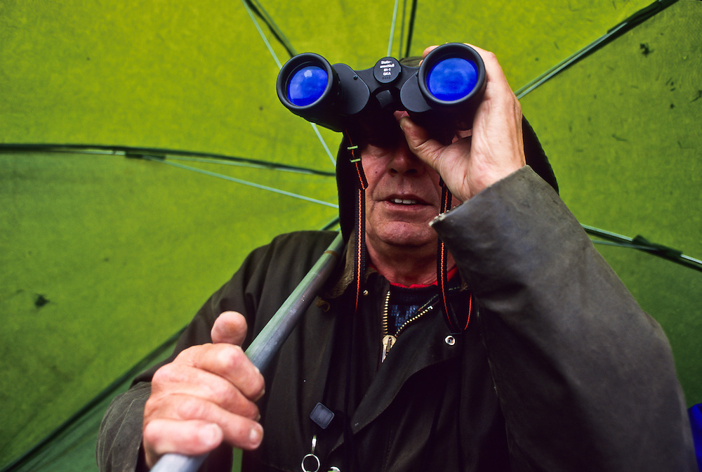A man looking out from under an umbrella.