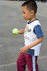 Young boy taking part in sports day competition in school playground,