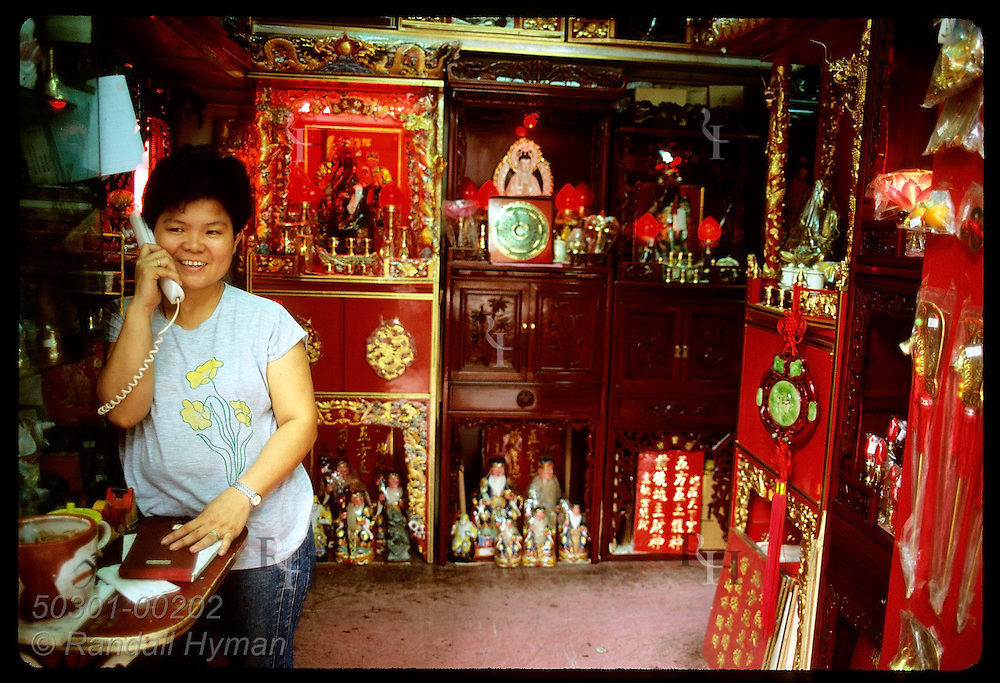 Woman talks on phone in her store that sells Feng Shui, Taoist and Buddhist items; Kowloon. Hong Kong