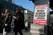On the day that the UK Governments Chief Scientific Advisor, Sir Patrick Vallance said that the Coronavirus Covid-19 outbreak was now spreading person to person in the UK, Londoners walk past the latest news headline from the capitals London Evening Standard newspaper outside Charing Cross railway station, on 6th March 2020, in London, England.