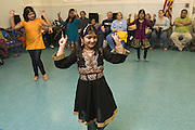 Dance students Arika Diwedi, 10, left, Kavya Nair, 10, Preeti Tanwani, 8, center, and Shloka Nair, 9, demonstrate Nachale: The Bollywood Dance Workout, during the English Conversation Club: Dance and Dialogue event Saturday April 9, 2011 at the Iroquois Branch of the Louisville Free Public Library in Louisville, Ky. Henna and Bindi followed the Bollywood dance lesson, and then volunteers were paired with English language learners to work on conversation skills. (Photo by Brian Bohannon)