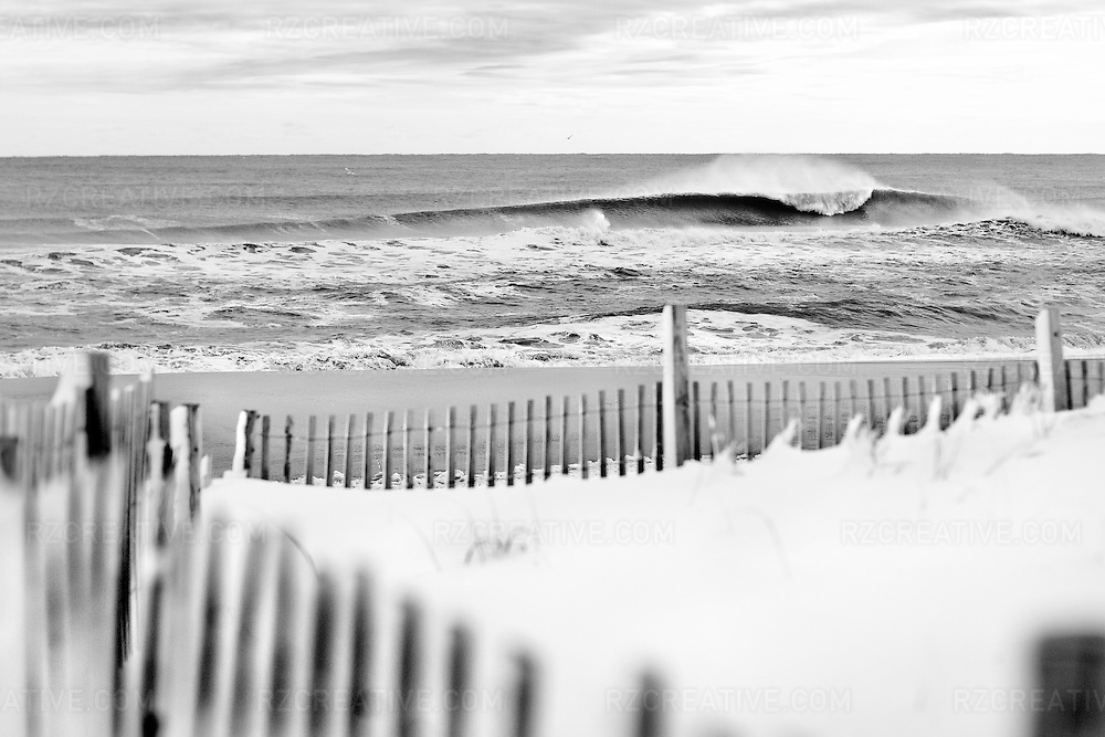 A wave breaks on a cold morning in the northeast with snow on the beach.