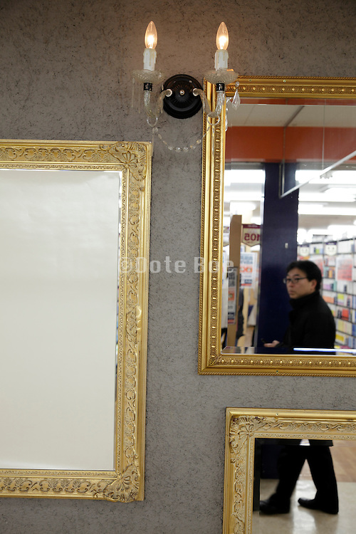 various decorative and gold leafed baroque style mirrors and frames on display in a department store