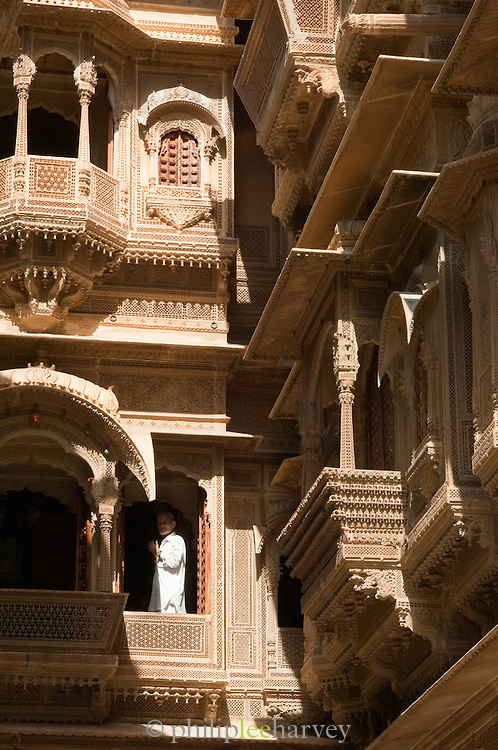 Man standing on a Jharokha, an Indian covered overhanging balcony at Jaisalmer Fort, the 'Golden Fort'. It is one of the largest forts in the world. Jaisalmer, Rajasthan, India