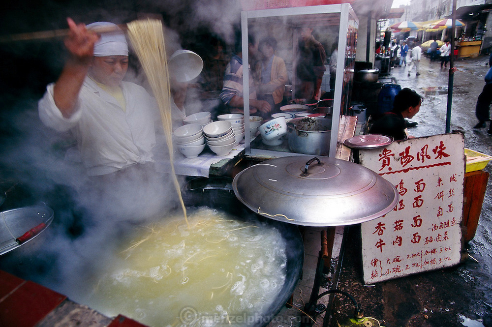 Steam rises in clouds from the huge woks of this noodle vendor in Kunming, in southwest China. Cooked in the celebrated style of the city of Guiyang, 300 miles away, these egg noodles are served in a spicy broth and topped with chicken, beef, shiitake mushrooms, or (most famously) pig intestines and blood. Hungry Planet: What the World Eats (p. 14).