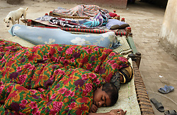 Mukhtar Mai, 33, sleeps next to her nephew, Yaqoub Ahmad, 4, outside her home, Meerwala, Pakistan, April 29, 2005. Mai, went against the Pakistani tradition of committing suicide when she brought charges against the men who gang raped her nearly three years ago. With money from the ruling she opened two schools, one for girls, the other for boys, citing that education is the only thing that will stop such acts from happening.