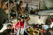 A food vendor and train staff squeeze through the congested second class compartment.<br /> Inside the Dibrugarh-Kanyakumari Vivek Express, the longest train route in the Indian Subcontinent. It joins Kanyakumari, Tamil Nadu, which is the southernmost tip of mainland India to Dibrugarh in Assam province, near the border with Burma.