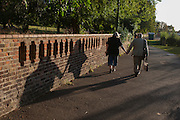 A devoted elderly couple hold hands as they walk in late afternoon sunshine through Ruskin Park, south London borough of Southwark, England UK.