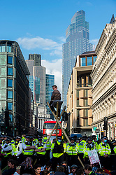 """© Licensed to London News Pictures. 27/08/2021. LONDON, UK.  Police officers surround a climate activist from Extinction Rebellion who has erected bamboo scaffolding during a protest blocking traffic on Queen Victoria Street and Cannon Street in The City of London.  The event is part of the 'Impossible Rebellion' protest to """"target the root cause of the climate and ecological crisis"""" and are ongoing for two weeks until the Government agrees to stop all new fossil fuel investments.  Photo credit: Stephen Chung/LNP"""