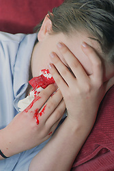 Young rape victim covering bleeding face crying,