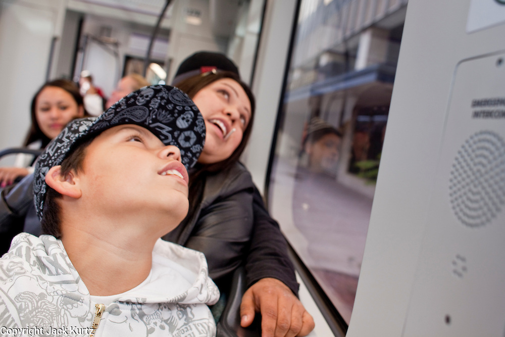 27 DECEMBER 2008 -- PHOENIX, AZ: At 10:04AM Angel Andazola (CQ) 11, and his mom, Yvonne Bojorquez (CQ) from Phoenix peer out the window of the train as it cruises through downtown Phoenix.  Metro Light Rail started running Saturday, Dec. 28. The light rail line is 20 miles long and cost $1.4 billion dollars. PHOTO BY JACK KURTZ
