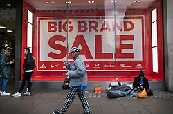 © Licensed to London News Pictures. 23/12/2016. London, UK. Shoppers look for bargains in Oxford Street as a homeless man sits outside a shop on the last working day before Christmas. Photo credit: Peter Macdiarmid/LNP