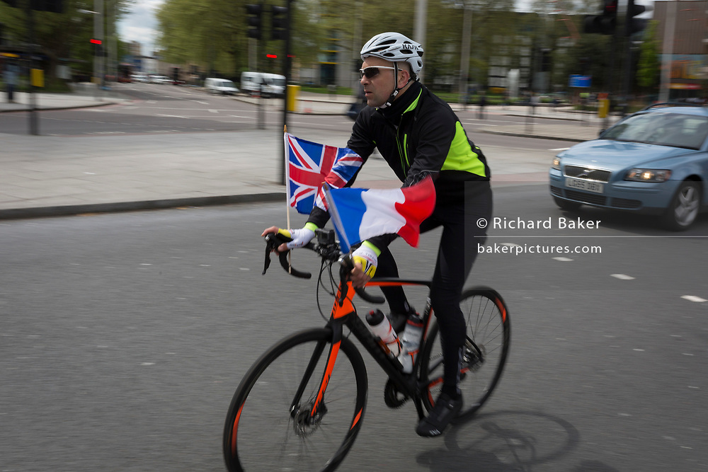 An Anglo-French cyclist flies the British Union Jack and French French Tricolour flags on his handelars as he cycles through south London, at Elephant And Castle, on 3rd May 2018, in London, UK.