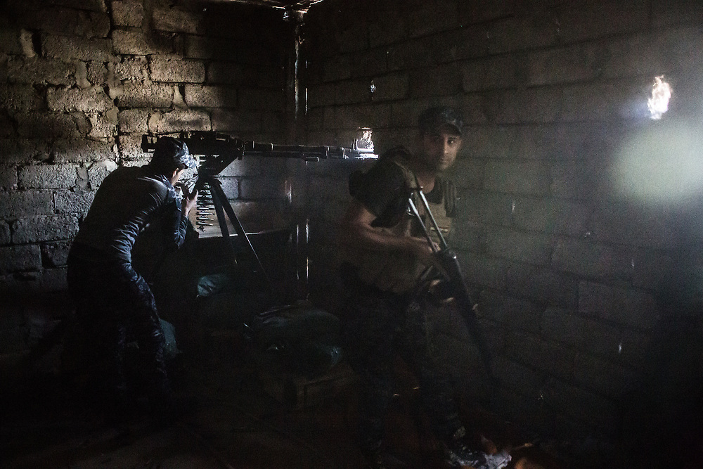 An Iraqi Federal Police officer fires a clip to ISIS's position at the front line in West Mosul, Iraq.<br />