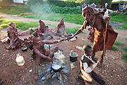 A Himba woman prepares a meal of cornmeal porridge in a vacant lot in Opuwo, northwestern Namibia. (From the book What I Eat: Around the World in 80 Diets.)  They had come  to Opuwo from Angola to get medical care for a family member who fell out of a tree and broke his arm.