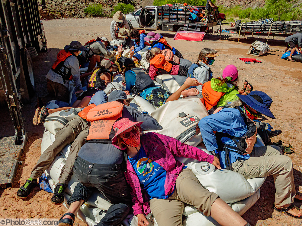 On the last of 16 days boating together for 226 miles, our group lay down on the job of raft deflation, at Diamond Creek on the Hualapai Indian Reservation, Arizona, USA. During this pandemic trip (April 3-18, 2021), masks were required during the initial meeting in Flagstaff, for bus rides, for initial embarkation at Lees Ferry, for serving lines at all meals, and for final disembarkation at Diamond Creek. Otherwise, our healthy outdoor raft trip was unencumbered by facial coverings. For this photo's licensing options, please inquire at PhotoSeek.com.