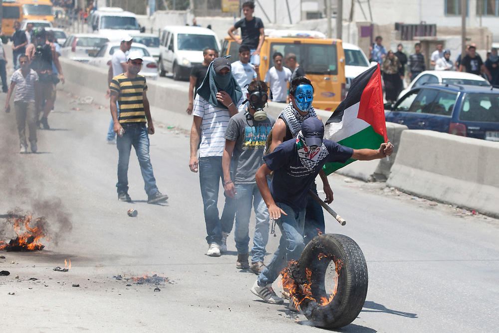 Palestinian demonstrators roll a burning tire at Israeli soldiers, not seen, during clashes with Israeli troops at the Qalandiya checkpoint, between Jerusalem and the West Bank city of Ramallah, on June 5, 2011. Palestinians Mark The 44th Anniversary of the 1967 Six Day War.