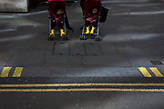 Two small children sleep in their respective buggies as unseen parents prepare to cross a street in the City of London. We see the repetition of yellow bars and parallel lines from the childrens' boots and parking restriction lines on the kerb and road. The street is in the City of London, the capital's financial heart and the kids' parents have been walking along Cannon Street, stopping to wait for a green pedestrian light to cross the road.