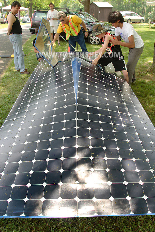 A Newburgh Free Academy student helps a boy into a solar car, which was on display at the Orange County Earth and Water Festival sponsored by Orange County, Orange Environment and the Orange County Water Authority on June 7, 2008. The car is powered by 470 solar panels.