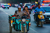 Three wheeled vehicles, Turpan, Xinjiang Province, China. Turpan is a small oasis town and former Silk Road outpost. Uyghur people are a Central Asian people of Muslim Turkic origin. They are China's largest minority group.