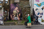 Local ladies walk past graffiti and urban artwork that features pandas and a childs face, on 20th January 2020, in Croydon, London, England.