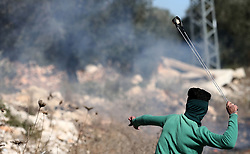 November 2, 2018 - Nablus, West Bank, Palestinian Territory - A Palestinian protester uses a slingshot to hurl stones towards Israeli forces during clashes following a weekly demonstration against the expropriation of Palestinian land by Israel in the village of Kfar Qaddum, near the West Bank city of Nablus.  (Credit Image: © Shadi Jarar'Ah/APA Images via ZUMA Wire)