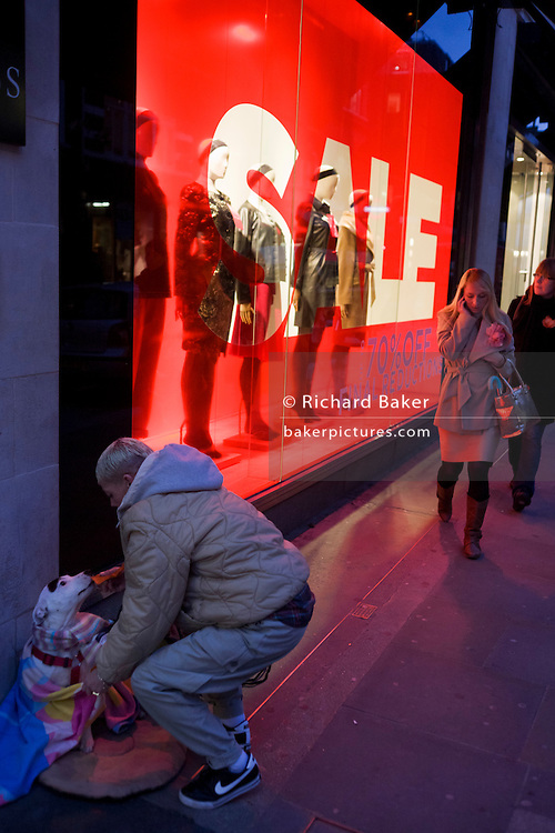 A Big Issue seller makes her pet dog comfortable on pavement outside clothing shop Hobbs in central London.