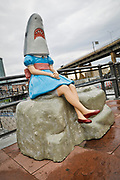 """SHOT 10/23/17 1:58:43 PM - Shark Girl, the painted fiberglass statue at Canalside in downtown Buffalo, N.Y. Shark Girl is the absurd, hilarious, and bittersweet creation of artist Casey Riordan Millard. While Shark Girl might appear sorrowful or lonely, there is also a comic element to this """"fish out of water."""" In Millard's first public sculpture, Shark Girl patiently waits, legs daintily crossed, hands folded, for a companion to join her. Buffalo, N.Y. is the second most populous city in the state of New York and is located in Western New York on the eastern shores of Lake Erie and at the head of the Niagara River. By 1900, Buffalo was the 8th largest city in the country, and went on to become a major railroad hub, the largest grain-milling center in the country and the home of the largest steel-making operation in the world. The latter part of the 20th Century saw a reversal of fortunes: by the year 1990 the city had fallen back below its 1900 population levels. (Photo by Marc Piscotty / © 2017)"""