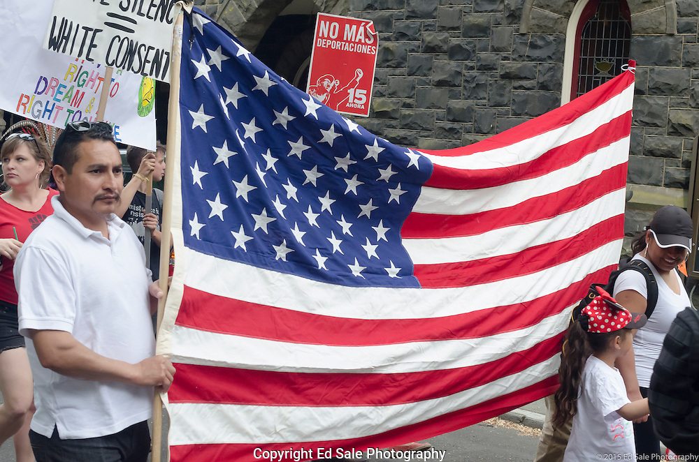 Demonstrators in 2015 May Day rally and march in Portland, Oregon holds a large  American Flag