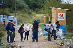 © London News Pictures. 10/08/2015. Calais, UK. Presenter SALLY MAGNUSSON (blonde hair and light jacket) taking part in Filming for BBC songs of Praise taking place in the migrants camp in Calais, France,  known as 'The Jungle'. The filming centred around a makeshift church built within the migrant camp. Songs of Praise is a religious BBC Television programme. Photo credit: Ben Cawthra/LNP