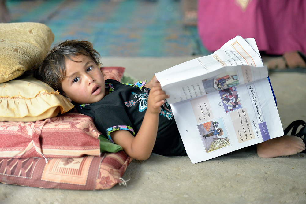 Four-year old Neama browses through a book in her family's transitional house in Beit Hanoun, Gaza. The house was provided by the local government after the family's home was destroyed by an Israeli air strike in 2014. The family received a water tank and hygiene supplies from International Orthodox Christian Charities, a member of the ACT Alliance. Before the water tank was installed, the children of the family had to walk 15 minutes to a United Nations school to carry back water. Now, according to their mother, they can spend their time studying.<br /> <br /> Parental consent obtained.