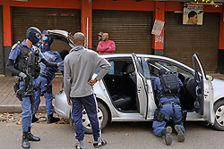 JOHANNESBURG, SOUTH AFRICA - APRIL 18: SAPS officers conduct a search during a South African Police Service (SAPS) Metro Police and Army supported patrol in Rockey Street, Yeoville. Random searchs and social distancing measures on April 18, 2020 in Johannesburg South Africa. Under pressure from a global pandemic. President Ramaphosa declared a 21 day national lockdown extended by another two weeks, mobilising goverment structures accross the nation to combat the rapidly spreading COVID-19 virus - the lockdown requires businesses to close and the public to stay at home during this period, unless part of approved essential services. (Photo by Dino Lloyd)
